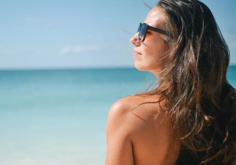jente i solen med solbriller og solbrun hud