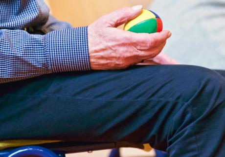 gammel mann holder en ball i hånden