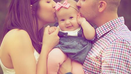 foreldre som kysser barnet på hodet