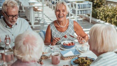 to eldre par spiser en sunn middag i godt humør